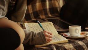Das Mädchen macht eine Aufzeichnung im Tagebuch stock video