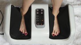 Das Mädchen macht eine Fußmassage unter Verwendung eines elektronischen Fuß Massager Der Schönheitsbegriff und die Gesundheit Ger stock video footage
