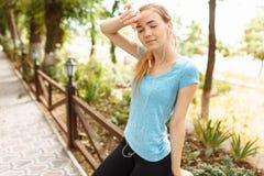Das Mädchen macht einen Bruch im Training, Rest von der Eignung und Betrieb auf der Straße lizenzfreies stockfoto