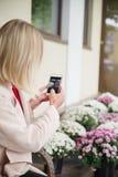Das Mädchen macht Fotos von Blumen outdoor Stockbild