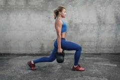 Das Mädchen macht Laufleinen mit kettlebells Stockfoto