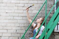 Das Mädchen macht das Vorbereiten für das Malen eines Holzoberfläche Gazebo, Zaun lizenzfreie stockbilder