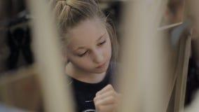 Das Mädchen malt ein Bild im Kind-` s Studio der schöner Kunst Viele Gestelle und Segeltuch auf dem Tisch stock footage