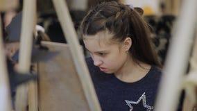 Das Mädchen malt ein Bild im Kind-` s Studio der schöner Kunst Viele Gestelle und Segeltuch auf dem Tisch stock video