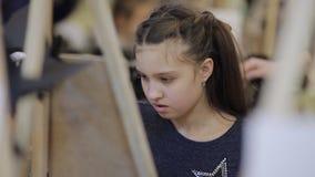 Das Mädchen malt ein Bild im Kind-` s Studio der schöner Kunst Viele Gestelle und Segeltuch auf dem Tisch stock video footage