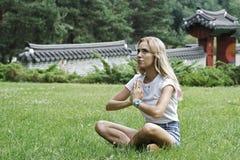 Das Mädchen meditiert im Park Stockbilder