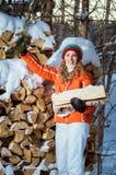 Das Mädchen mit Brennholz im Winter stockbild