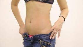 Das Mädchen mit dünner Zahl der dünnen Taille mit aufgeknöpften Jeans auf einem weißen Hintergrund stock video