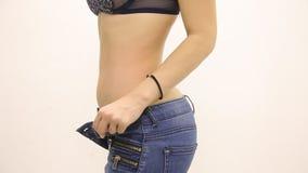 Das Mädchen mit dünner Zahl der dünnen Taille mit aufgeknöpften Jeans auf einem weißen Hintergrund stock footage