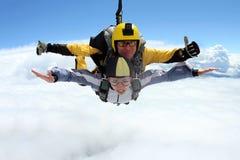 Das Mädchen mit dem Ausbilder im freien Fall Im freien Fall springen im blauen Himmel stockfotografie
