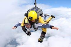 Das Mädchen mit dem Ausbilder im freien Fall Im freien Fall springen im blauen Himmel lizenzfreies stockfoto