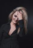 Das Mädchen mit dem blonden Haar auf schwarzem Hintergrund Stockfotografie