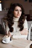 Das Mädchen mit dem dunklen Haar an einem Tisch im Restaurant Warten auf meine Bestellung des Kakaos Gelocktes Haar, schönes Make Lizenzfreie Stockbilder