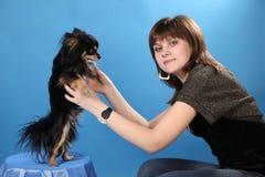 Das Mädchen mit dem Hündchen auf einem blauen Hintergrund Lizenzfreies Stockfoto