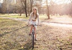 Das Mädchen mit dem Kranz auf dem Kopf durch Fahrrad Stockfoto
