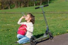Das Mädchen mit dem Roller trinkt etwas Wasser Lizenzfreies Stockfoto