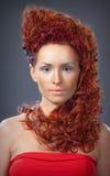 Das Mädchen mit dem roten Haar in einer roten Kleidernahaufnahme Stockfotos