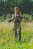 Das Mädchen mit dem roten Haar kommt aus das Holz mit einem Gewehr in seiner Hand heraus Lizenzfreie Stockfotografie