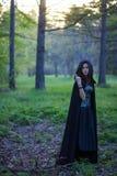 Das Mädchen mit dem schwarzen Mantel im Wald lizenzfreie stockbilder