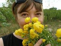 Das Mädchen mit den ersten Frühlingsblumen globeflowers Maifeiertag Stockbilder
