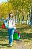 Das Mädchen mit den mehrfarbigen Paketen, die auf Park gehen Stockbild