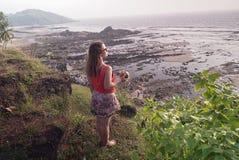 Das Mädchen mit der Kokosnuss betrachtet die schöne Ansicht Lizenzfreie Stockfotos