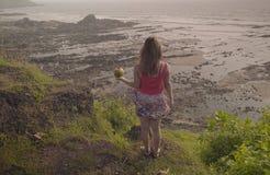 Das Mädchen mit der Kokosnuss betrachtet die schöne Ansicht Lizenzfreie Stockbilder