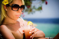Das Mädchen mit einem Cocktail nahe dem Meer Stockbild