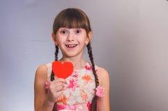 Das Mädchen mit einem Herzen lächelt Stockfoto