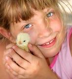 Das Mädchen mit einem Huhn in den Händen. Stockbild