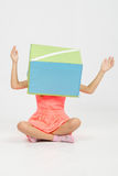Das Mädchen mit einem Kasten auf seinem Kopf ihre Arme Lizenzfreies Stockfoto