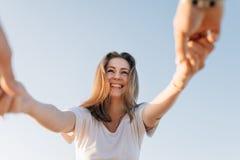 Das Mädchen, mit einem Lächeln, hält Hände Stockfotos