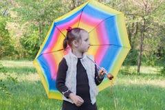 Das Mädchen mit einem mehrfarbigen Regenschirm Stockfoto