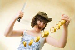 Das Mädchen mit einem Messer und einer Banane Stockfoto