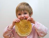 Das Mädchen mit einem Pfannkuchen Lizenzfreies Stockfoto