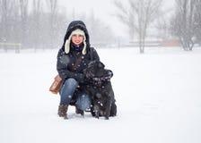 Das Mädchen mit einem schwarzen Hund auf dem Schneefeld Lizenzfreies Stockbild