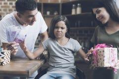 Das Mädchen mit Ekel stößt die Geschenke ab und Geld bot sie durch die Eltern an Lizenzfreies Stockfoto