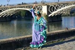 Das Mädchen mit Flamencokleidertanzen unter der Brücke von Triana, Sevilla, Spanien Stockfotos