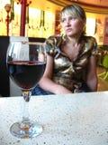 Das Mädchen mit Glas Rotwein im Restaurant Stockbilder