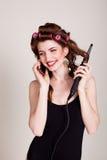 Das Mädchen mit Haarlockenwicklern sprechend am Telefon und macht die Frisur stockfotografie
