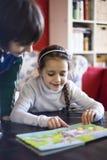 das Mädchen mit 5-Jährigen betrachtet ein Buch mit Zahlen Stockbild