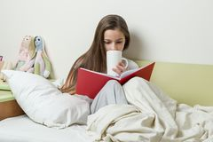 das Mädchen mit 10-Jährigen in den Pyjamas liest Buch und hält Tasse Tee Lizenzfreies Stockbild