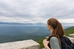 Das Mädchen mit Rucksack steht auf den Berg und die Inspektion Lizenzfreie Stockfotos