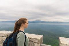 Das Mädchen mit Rucksack steht auf den Berg und die Inspektion Stockbilder