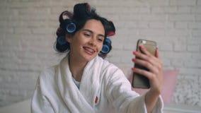 Das Mädchen nach der Dusche sitzt in einem Bademantel mit Lockenwicklern und steht am Telefon in Verbindung stock video footage