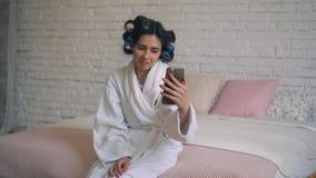 Das Mädchen nach der Dusche sitzt in einem Bademantel mit Lockenwicklern und steht am Telefon in Verbindung stock video