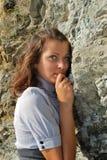 Das Mädchen nahe einem Felsen stockbilder