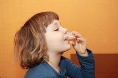 Das Mädchen nimmt die Medizin. Er trinkt Sirup Stockfotografie