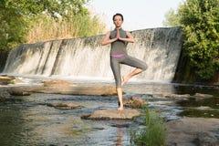 Das Mädchen nimmt Yoga durch das Wasser auf lizenzfreies stockfoto