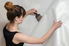 Das Mädchen reißt die alte Tapete von der Betonmauer auseinander und hält eine Spachtel lizenzfreies stockbild